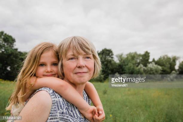 grandmother giving granddaughter a piggyback ride - british granny stock photos and pictures