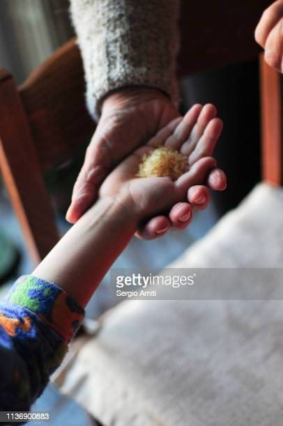 Grandmother giving rice grains to child