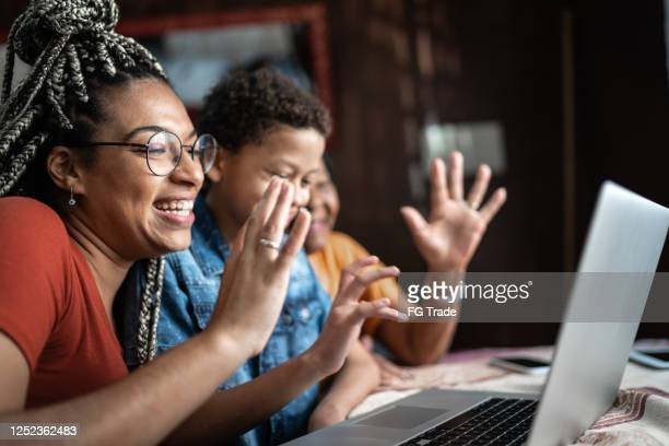 grandmother, granddaughter and grandson doing a video conference on laptop at home - candid forum stock pictures, royalty-free photos & images