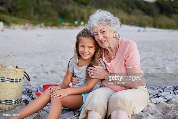 Grandmother & granddaughter sitting on beach