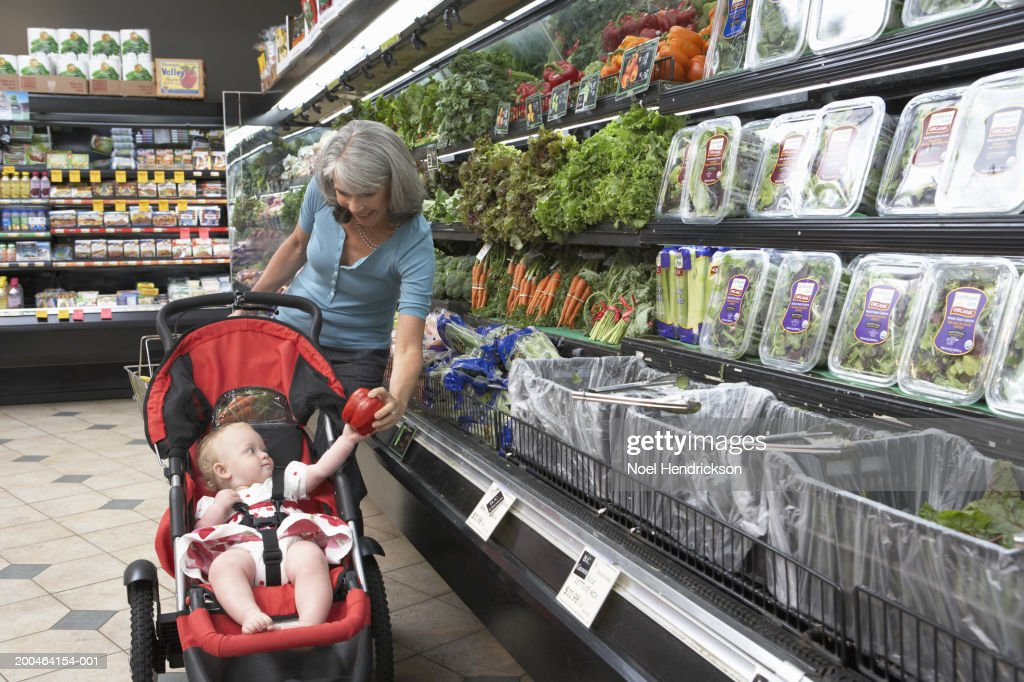 Grandmother handing baby girl (9-12 months) sweet pepper, close-up : Stock Photo