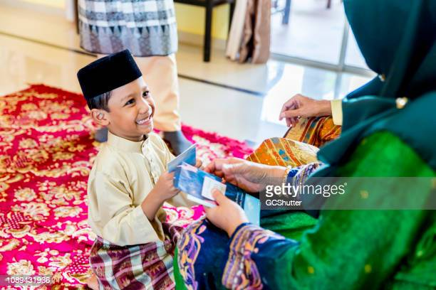 grandmother handing her grandson an envelope of money as a gift - beautiful ramadan stock pictures, royalty-free photos & images