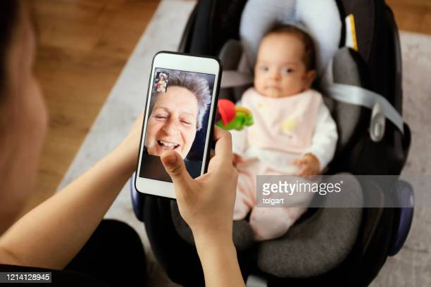 grandmother having video call with granddaughter - homemaker stock pictures, royalty-free photos & images