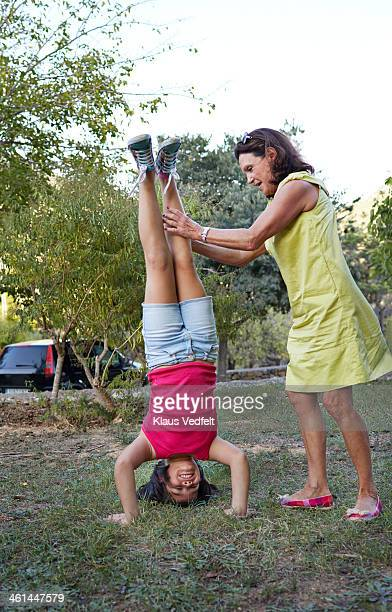 grandmother helping child with handstand - girl in dress doing handstand stockfoto's en -beelden