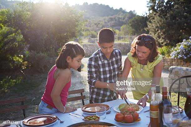 grandmother helping grandchildren with food - klaus vedfelt mallorca stock pictures, royalty-free photos & images