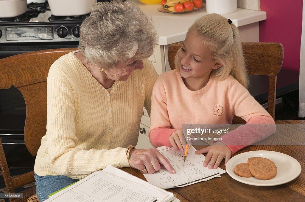 Grandmother helping granddaughter with homework : Stockfoto