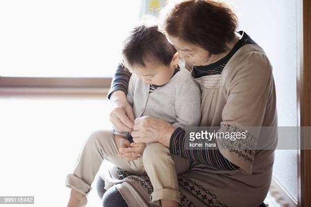 彼の服を変更する彼女の孫を助ける祖母