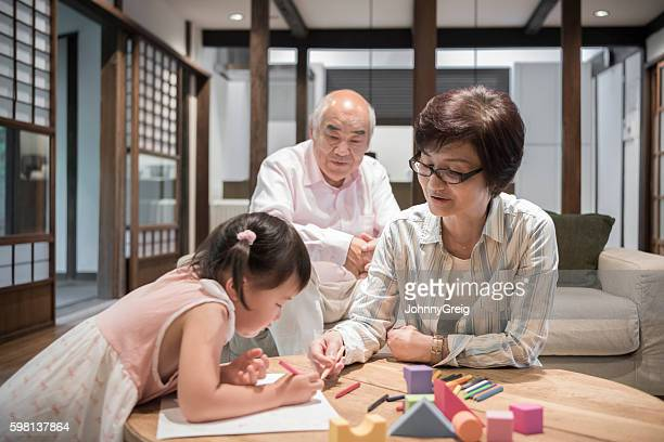 Grandmother helping Japanese girl with homework
