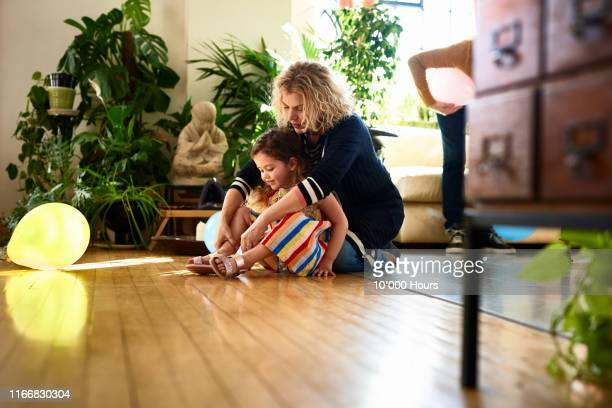 grandmother helping young girl to put on shoes - weekend activities stock pictures, royalty-free photos & images