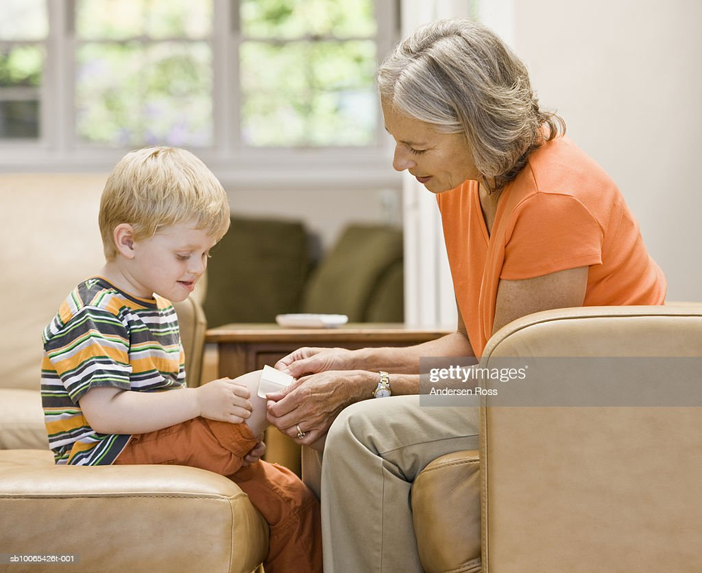 Grandmother helps grandson (2-3 years) apply bandage : Foto stock