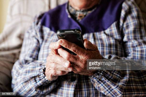 Grandmother holding a smartphone in the sofa