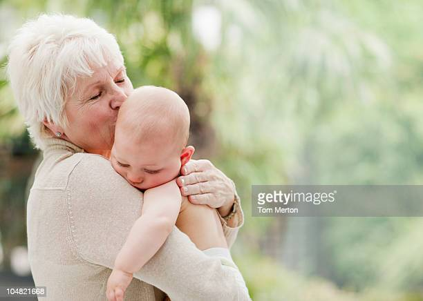 Grandmother holding and kissing baby