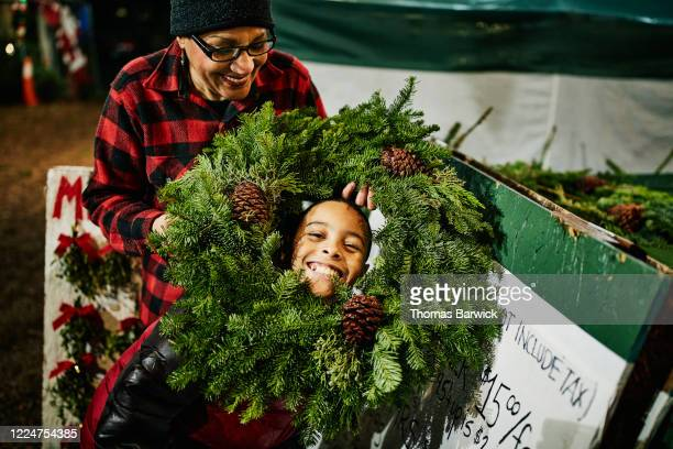 grandmother holding christmas wreath around smiling grandson - family stock pictures, royalty-free photos & images