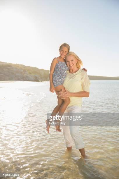 Grandmother holding granddaughter in waves