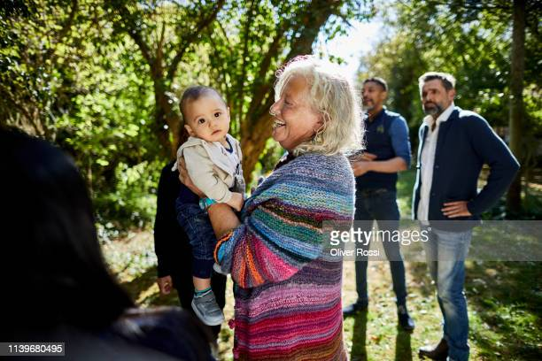 grandmother holding grandson on a garden party - linda oliver fotografías e imágenes de stock