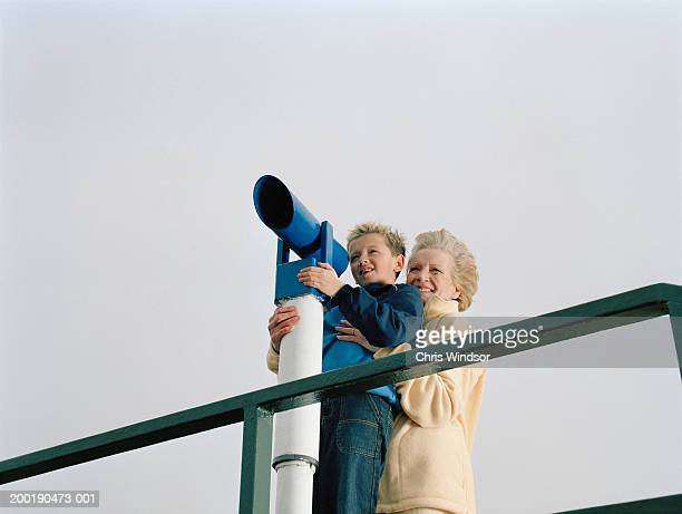 Grandmother holding grandson (3-5) up to telescope, smiling