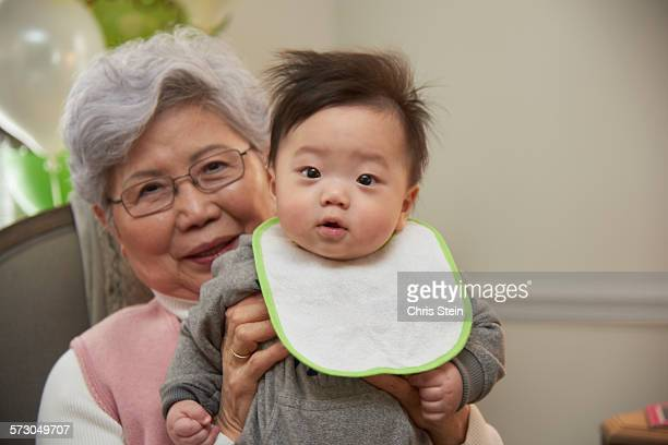 grandmother holding her baby grandson - scarsdale stock photos and pictures