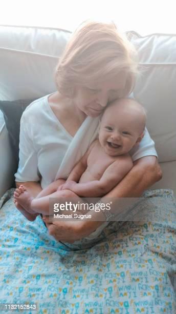 Grandmother holding smiling newborn granddaughter.