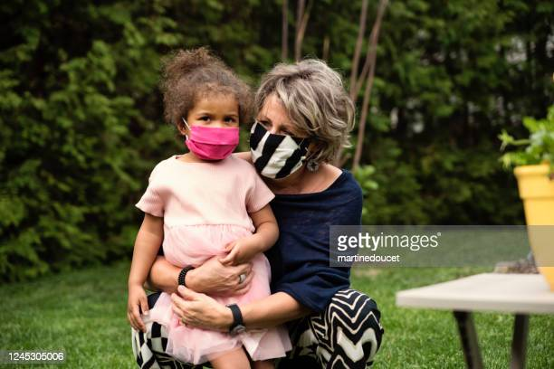 "grandmother holding toddler granddaughter with protective mask. - ""martine doucet"" or martinedoucet stock pictures, royalty-free photos & images"