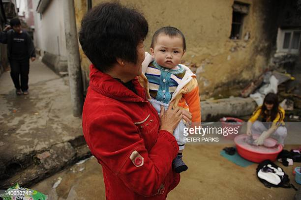 Grandmother holds her grandchild as her mother washes clothes at a well in Wukan where voting in village elections is taking place on March 4, 2012....