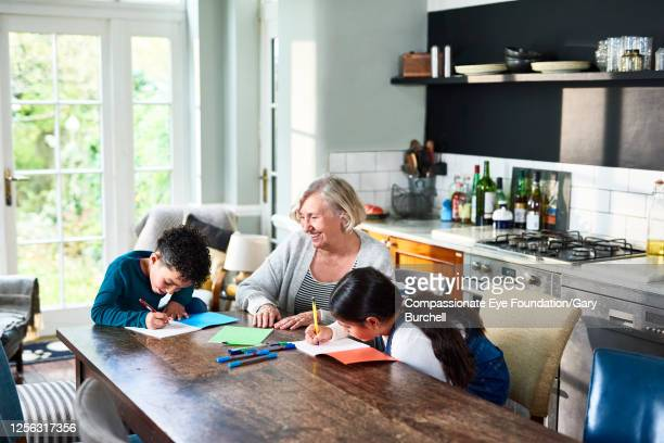 grandmother homeschooling grandchildren at dining table - photography stock pictures, royalty-free photos & images