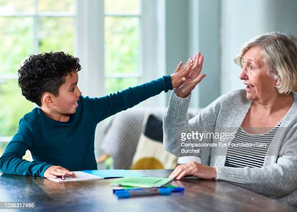 grandmother homeschooling grandson at dining table high fiving - retirement stock pictures, royalty-free photos & images
