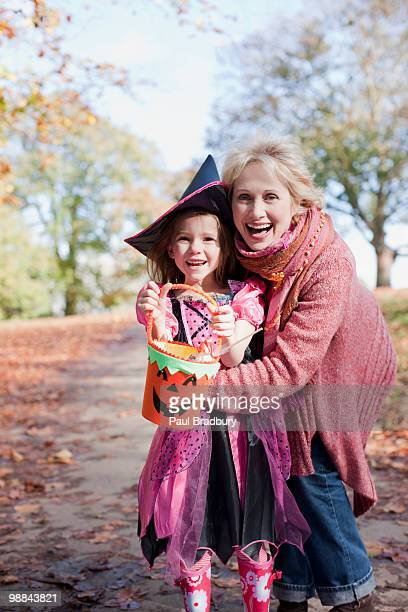 grandmother hugging granddaughter in halloween costume - british granny stock photos and pictures