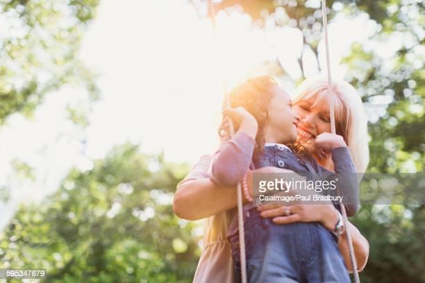 Grandmother hugging granddaughter on swing