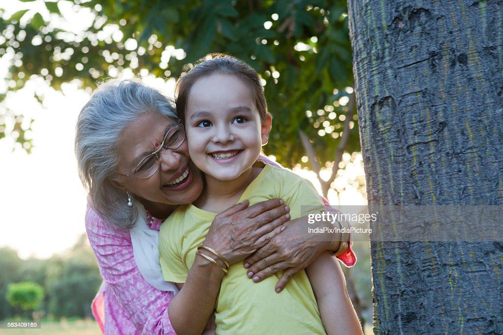 Grandmother hugging granddaughter : Stock Photo