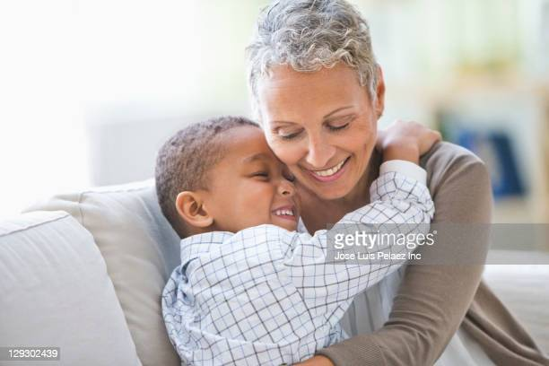 grandmother hugging grandson - black granny stock photos and pictures