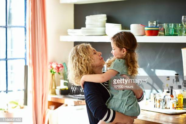 grandmother hugging little girl in school uniform in kitchen - embracing stock pictures, royalty-free photos & images