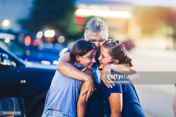 grandmother hugging two of her granddaughters at night during independence day celebration - diritti umani foto e immagini stock