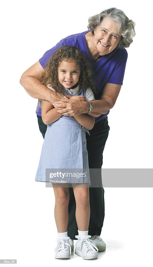 Grandmother hugs her granddaughter while they smile at the camera. : Foto de stock