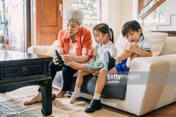 grandmother is helping her grandsons to putting on shoes - school girl shoes stock pictures, royalty-free photos & images