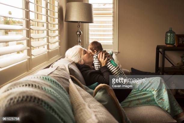 Grandmother kissing baby grandson on sofa at home