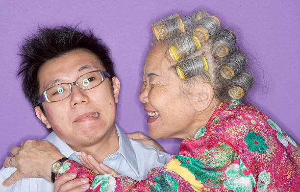 grandmother kissing grandson. - angry old asian lady stock pictures, royalty-free photos & images