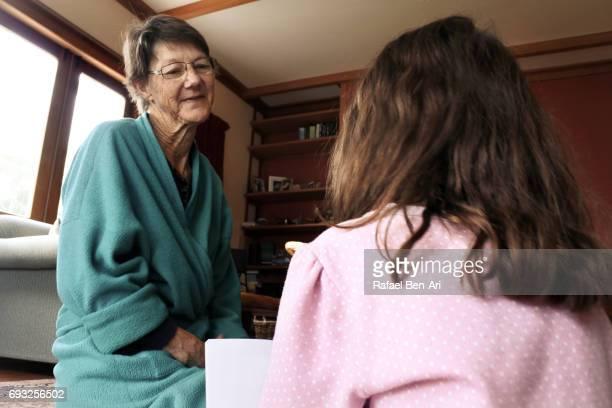 grandmother listens to her granddaughter - rafael ben ari fotografías e imágenes de stock