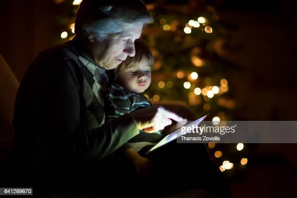 Grandmother looking a digital tablet with her grandchildren