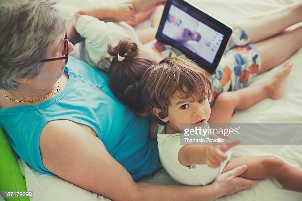 Grandmother looking a tablet with her grandchildre
