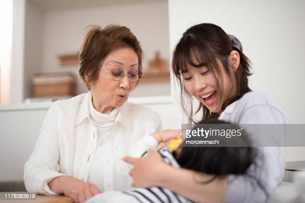grandmother looking at baby drinking bottle of milk - mother in law stock pictures, royalty-free photos & images