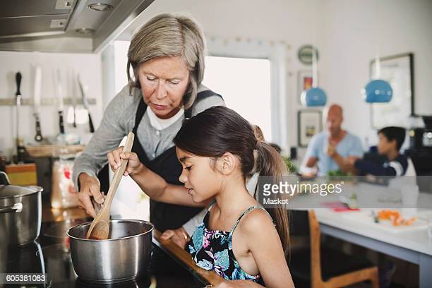 Grandmother looking at girl cooking at kitchen counter