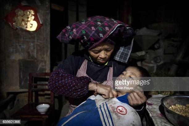 Grandmother Lu Guoxiu rubs warm water on the throat of grandson 'left behind' child Luo Lie to help with his cough on December 15 2016 in Anshun...