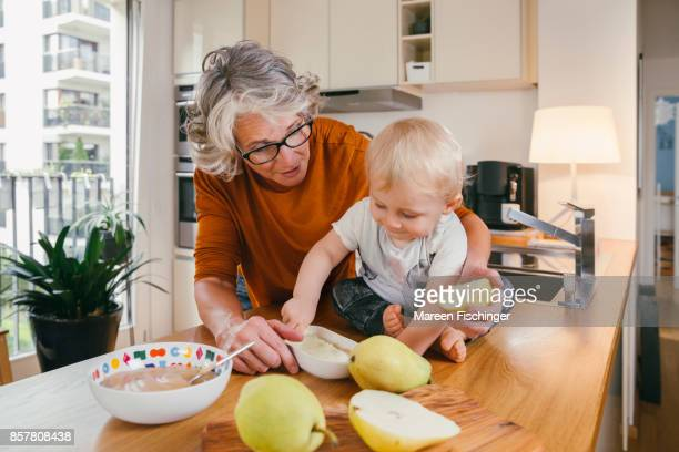 Grandmother making pear puree with her baby grandchild