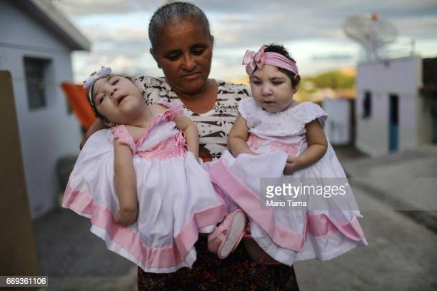 Grandmother Maria Jose holds her twin granddaughters Heloisa and Heloa Barbosa, both born with microcephaly, in front of their house as they pose for...