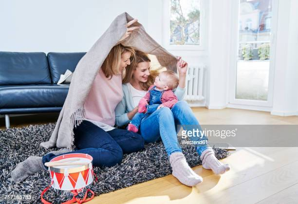 Grandmother, mother and baby girl playing in living room