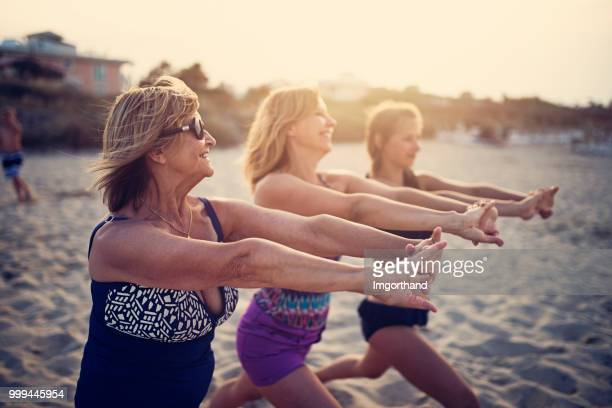 Grandmother, mother and daughter exercising on beach.