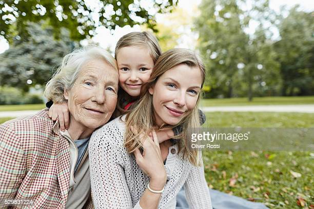 Grandmother, mother and daughter hugging in park