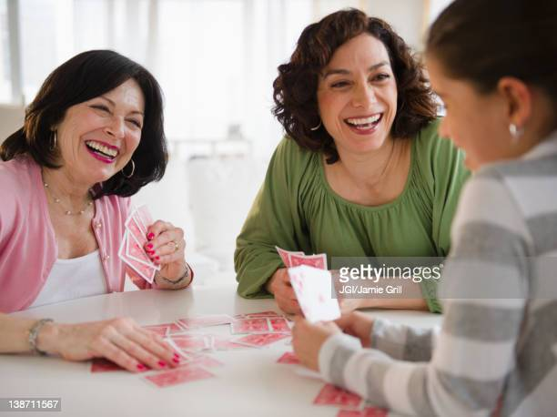 Grandmother, mother and daughter playing cards