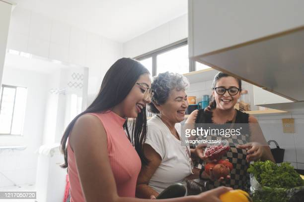 grandmother, mother and daughter unpacking groceries in the kitchen - latin american and hispanic ethnicity stock pictures, royalty-free photos & images