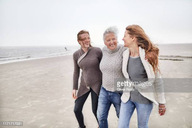 grandmother, mother and daughter walking on the beach - three people stock pictures, royalty-free photos & images